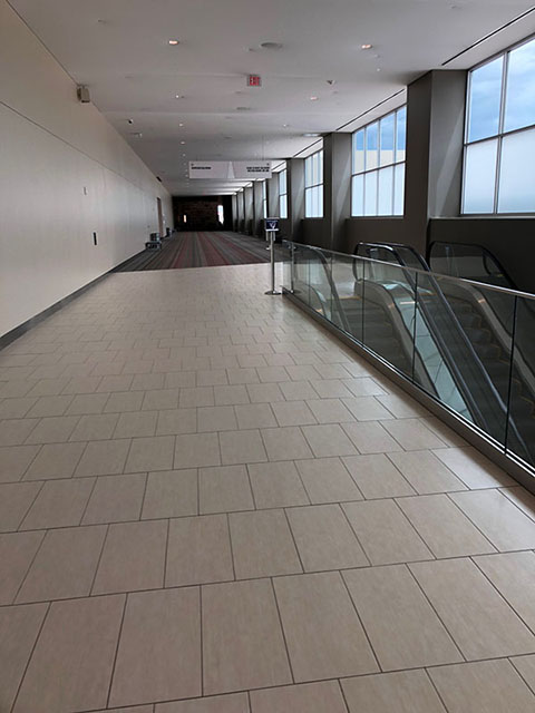 This photo shows a hallway. Extending approximately halfway down the hallway are rectangular beige tiles and then a gray and red striped carpet. On the left in this photo are escalators that lead down to the Meeting Room level.