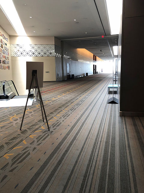 This hallway is completely carpeted in a pattern of light blue and gray stripes. On the left in this photo is an escalator that leads down to the Meeting Room level.