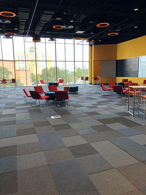This is a photo of a large meeting room called the Cantilever Room. The carpet is made up of squares in varying shades of gray. The walls are yellow with floor-to-ceiling windows along one side. There are various types of seating in this space from low armchairs to high barstool-type chairs.