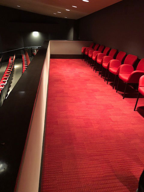 This photo shows a balcony with red armchairs and red carpeting.