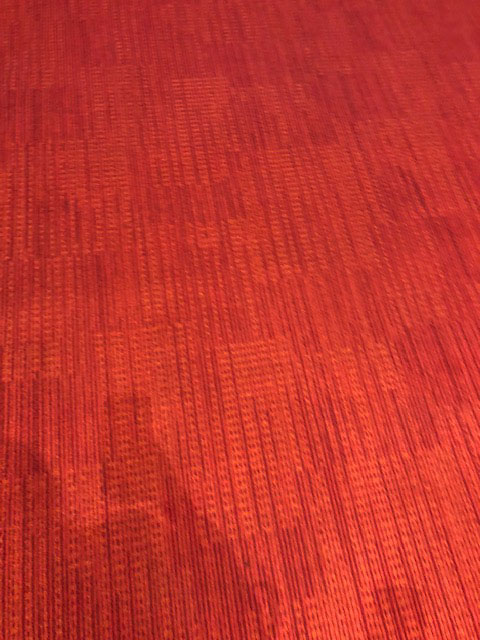 The photo shows a bright red textured carpet.