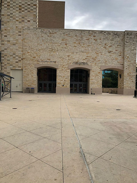 This photo shows a beige cement landing, leading up to a beige stone wall with three dark entryways. The entry on the leftmost side has text above it reading Lila Cockrell Theatre. The middle entry has text above reading Henry B. González Convention Center. The rightmost entry leads to a side outdoor porch and stairs to the River level.