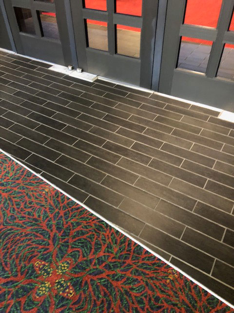 The hallway carpet ends approximately three feet before the doorway entrance. This photo shows thin rectangular black tile before the Lila Cockrell Theatre entrance.