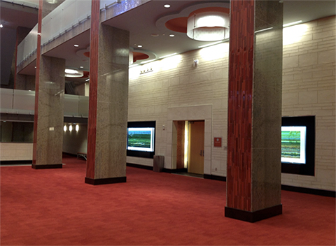 This photo shows the Lila Cockrell Theatre lobby. It has red carpet and rectangular granite columns. The entrance doors to the theater are interspersed through the lobby, are a light brown wood, and are located along a white tile wall.