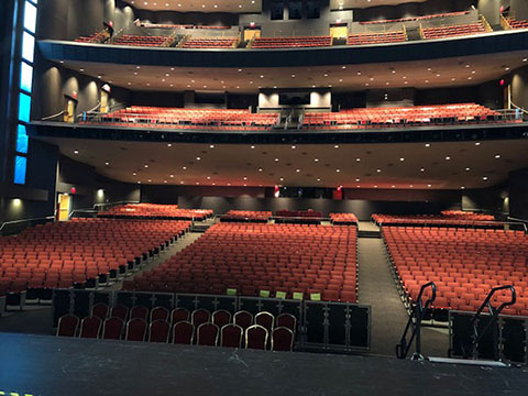 In the Lila Cockrell Theatre, there are three tiers of seating. All the chairs are upholstered in red, and the carpet in the aisles is gray.