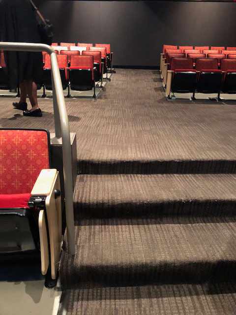 This photo shows the three steps in the aisle of the Lila Cockrell Theatre on the orchestra level. The carpet in the aisle is gray with lighter gray stripes.