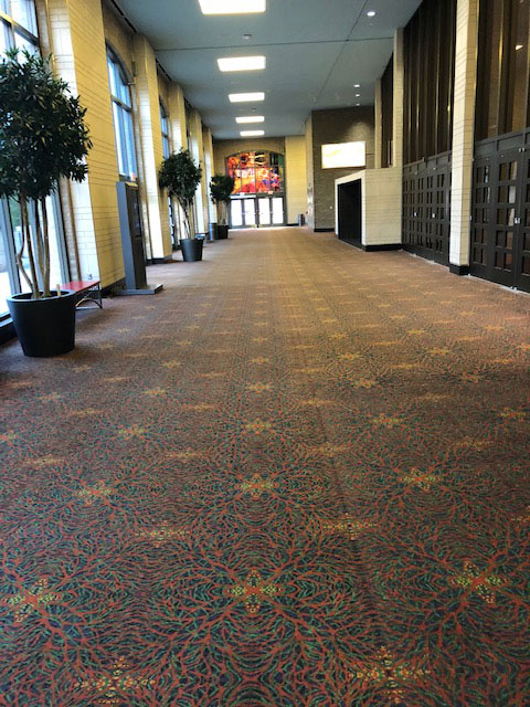 This photo shows a hallway leading from the entrance off Alamo Street to the West Lobby of the Convention Center. On the right of this photo are black doors leading to the Lila Cockrell Theatre.