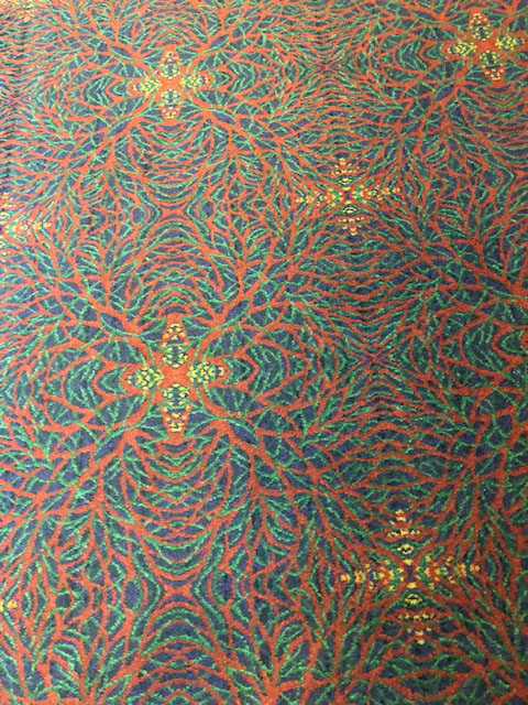 The carpet is a pattern of orange, green, and blue, with yellow stars interspersed.