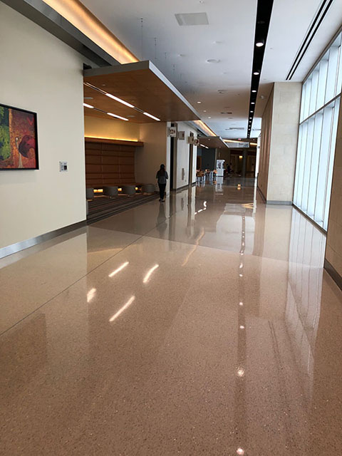 This photo shows the hallway between the Main Lobby and the West Lobby. The floor, like that in the Main Lobby, is made up of large beige speckled tiles. There are built-in seating areas on the left-hand side of the hallway that include benches, armchairs, and other mixed seating options. The nursing mothers' room is also on the left of the hallway and has a sign posted above the door with a graphic indicating a mother and infant.