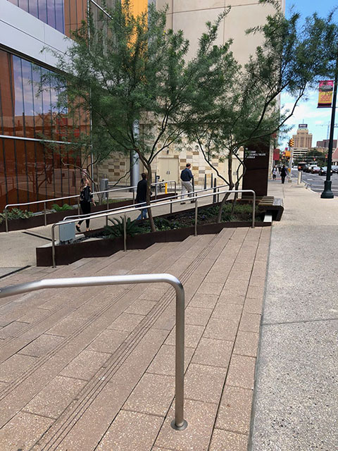 This photo shows a set of stairs from the Market Street sidewalk down to the plaza outside of the main entrance to the convention center. On either side of the stairs are silver handrails. Also in this photo is a ramp from the sidewalk down to the main entrance of the convention center. The ramp also has silver handrails on either side.