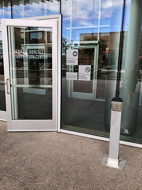 This photo shows a glass entry door to the convention center. There is a short pole to the right of the doorway with a wheelchair button.
