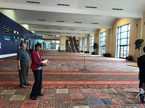 This photo shows a wide hallway with meeting rooms on the left side. The carpet is made up of individual squares, each with a unique pattern. There are also armchairs and couches on the left-hand side and doors leading out to a patio.