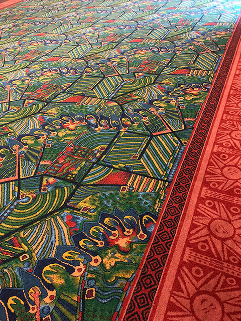 The carpet is a unique pattern of greens, yellows, and reds, all outlined by a red border.