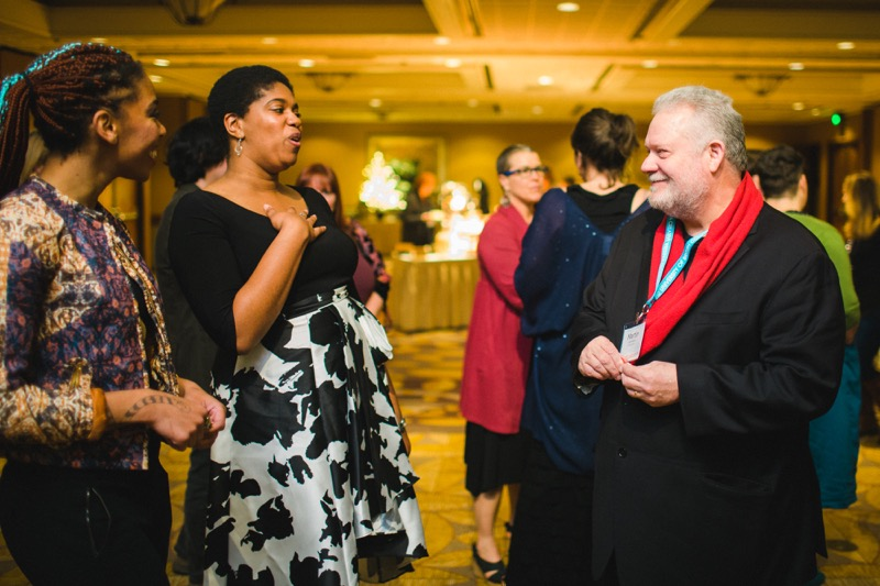 Martin Lammon, founder of the Donald Hall Prize, talks to two guests (Black women dressed in evening attire) at the 2019 AWP Gala