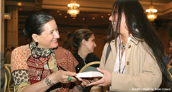 Author Sandra Cisneros hands a signed copy of her book to a smiling conference attendee