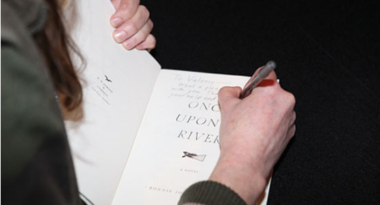 Author signing the title page of the novel Once Upon A River