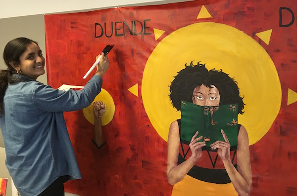 An artist paiting the image of a Latina woman reading against a red background and a yellow sun.
