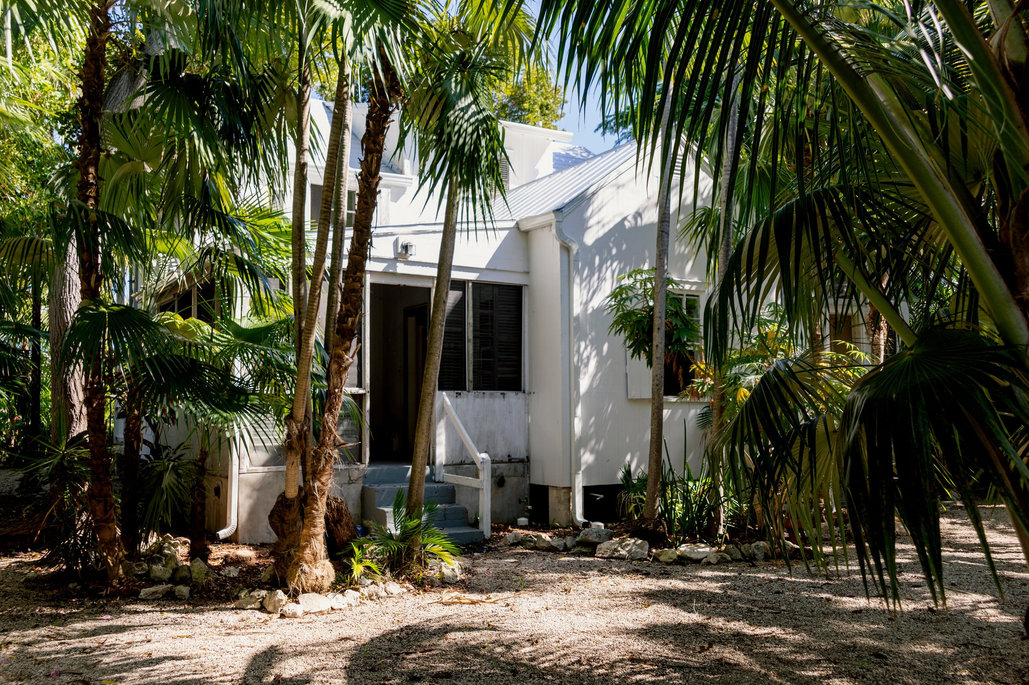 Bishop House in Key West, a white house standing behind palm trees