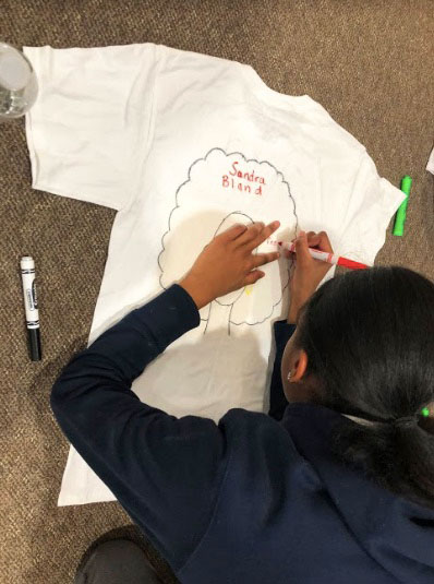 A student draws on a t-shirt