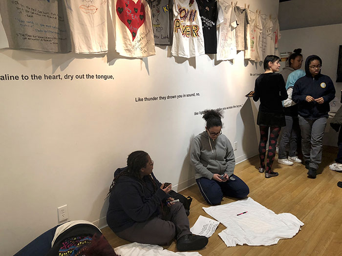 Students sit by a white wall with words, assembling their creations